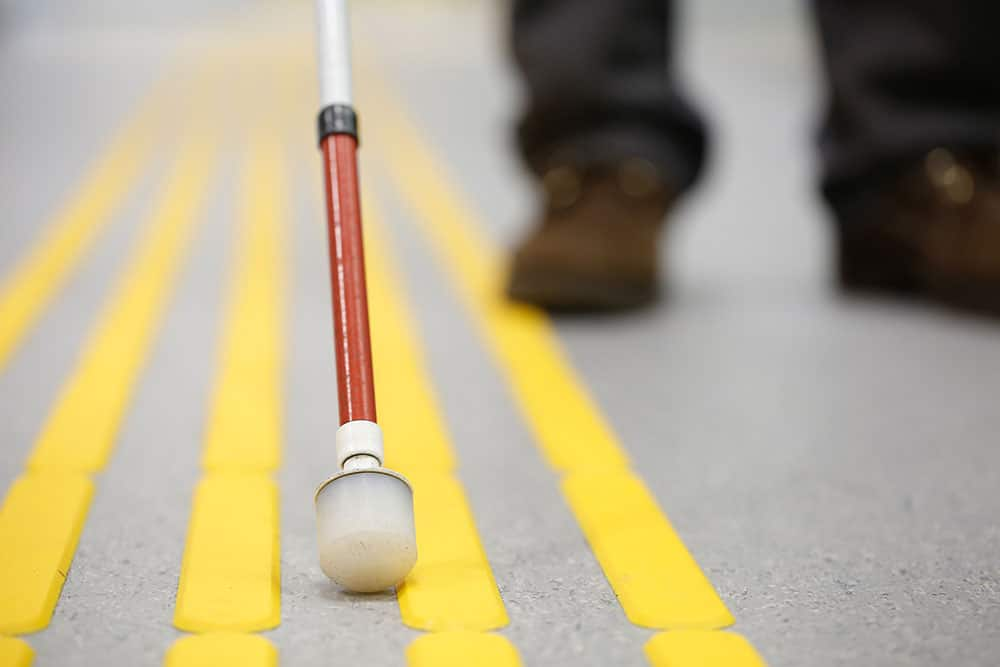 Cane sitting between ridged yellow lines, with person's feet in the background
